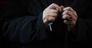 sacerdote sosteniendo rosario en la mano oracion traje negro