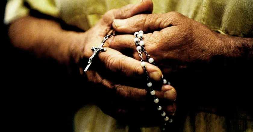sosteniendo un rosario entre las manos rezando rosario en un autobus