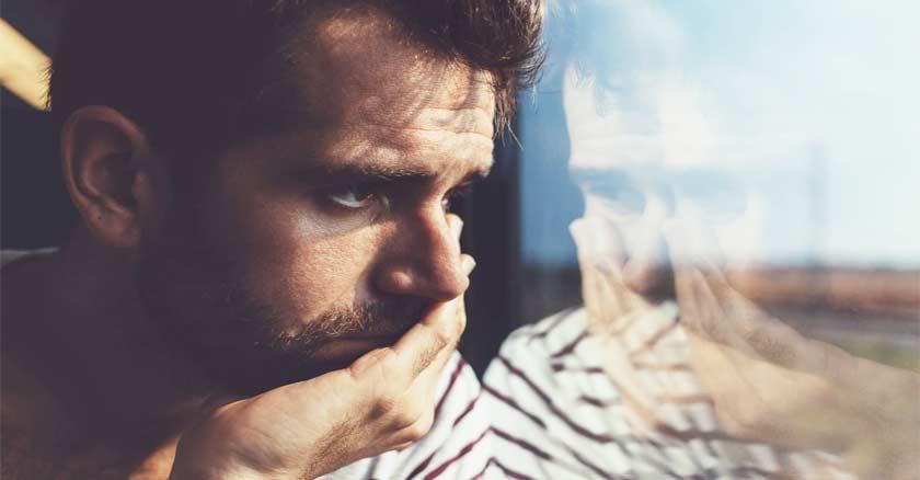 hombre-mirando-por-la-ventana-rostro-preocupado-angustiado-reflejo.jpg