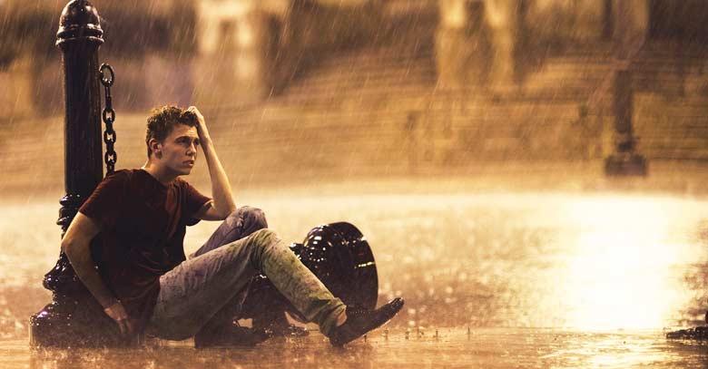 joven sentado en acera calle bajo la lluvia mojado