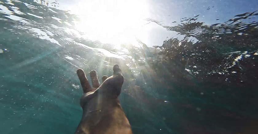 mano de persona bajo el agua intentando pedir ayuda a dios