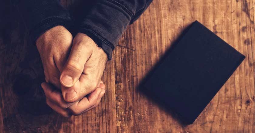 manos juntas orando sobre una mesa de madera biblia