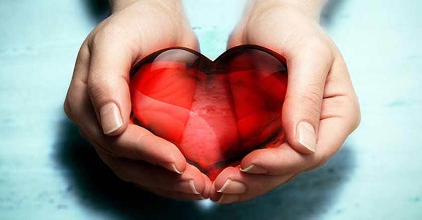 manos sosteniendo un corazon rojo de cristal fondo azul claro