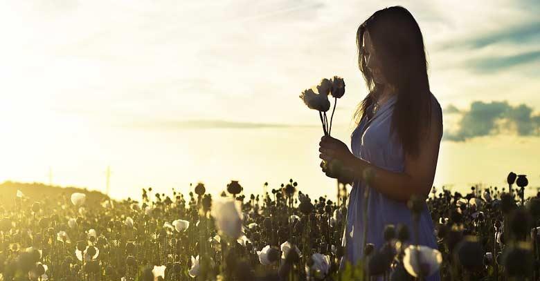 mujer en jardin natural recogiendo flores en la mano atardecer luz del sol
