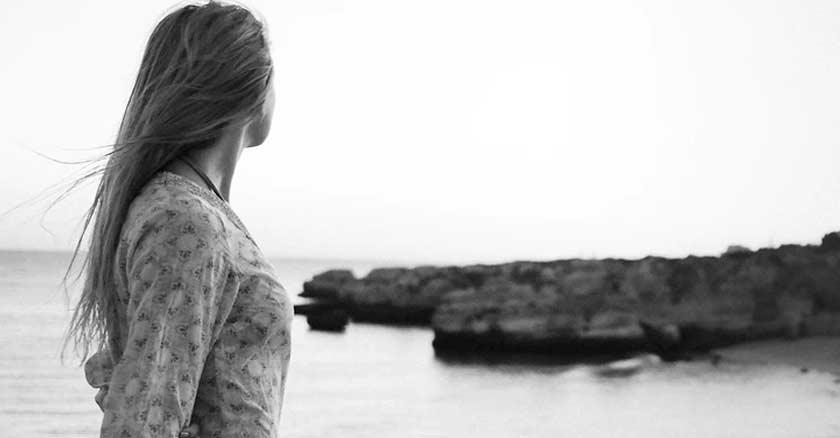 mujer en la orilla del mar viendo hacia el horizonte piedras