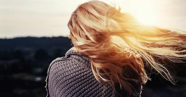 mujer espalda horizonte sol