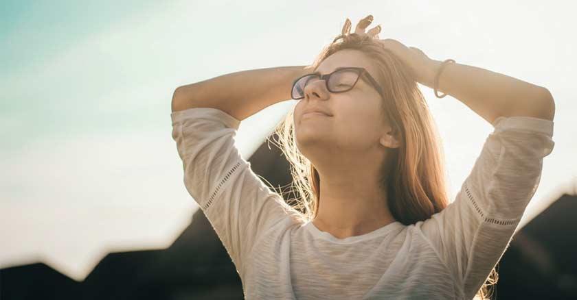 mujer-relajda-con-los-ojos-cerrados-al-aire-libre-fondo-naturaleza.jpg