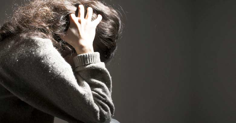 mujer tomando la cabeza con sus manos sufriendo sufrimiendo fondo oscuro