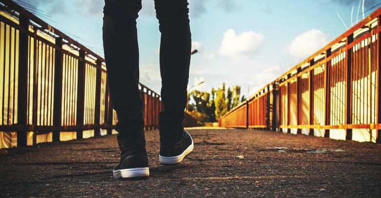 piernas de joven caminando hacia puente