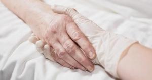 manos de doctor sosteniendo mano de enfermo muriendo en cama