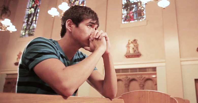 joven rezando con manos juntas dentro deiglesia catolica de rodillas