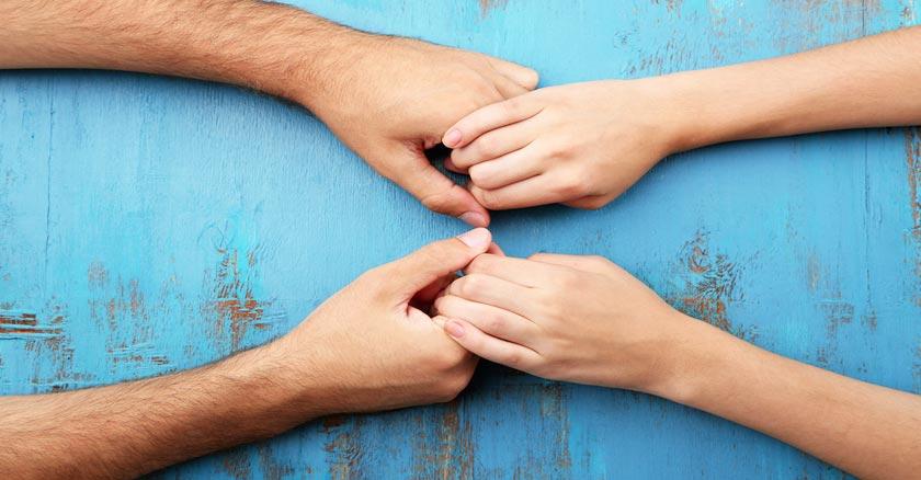 manos de esposo y esposa tocandose sobre una mesa de madera azul