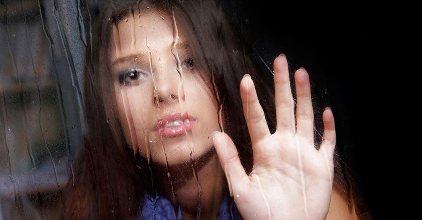 mujer triste observando a traves de una ventana de cristal gotas de lluvia