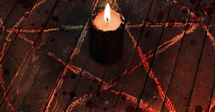 velta encendida en medio de rito satanico cruz de david demonio